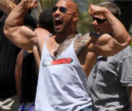 the rock arms flexing his biceps and showing his tatoo