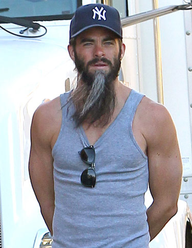 Chris Pine physique showing off his arms, shoulders with a large beard