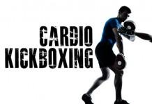 cardio kickboxing woman kicking a trainer