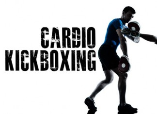 cardio kickboxing woman kicking a trainer